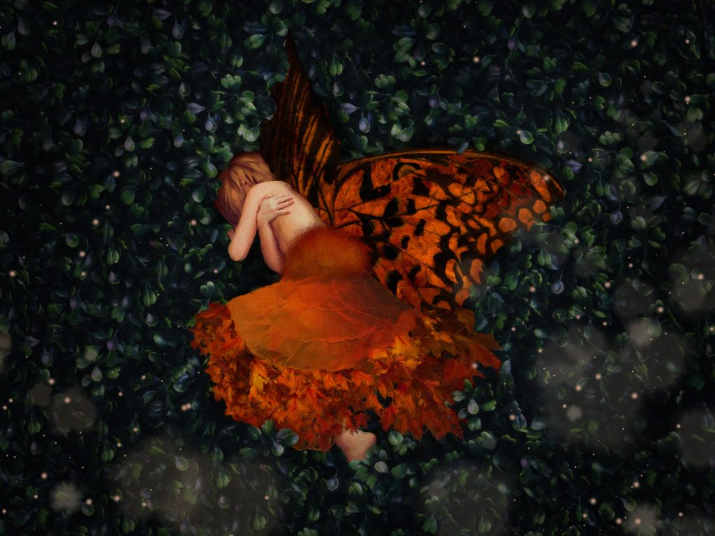 a fairy like an autumn maple leaf, laying in grass